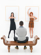 man entertained by two women in an art gallery