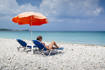 Sun lounger and umbrella on empty rock beach