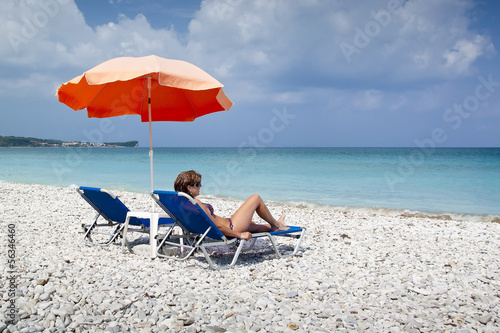 Sun lounger and umbrella on empty rock beach