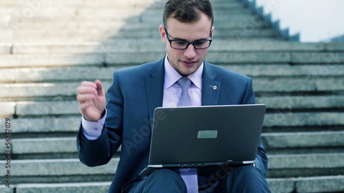 Angry businessman working on laptop in the city