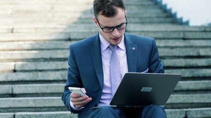 Young businessman working with smartphone and laptop on stairs