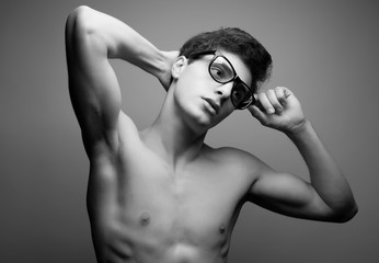 Handsome muscular male model with nice body wearing glasses
