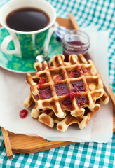 Breakfast with belgian waffles with jam and coffee