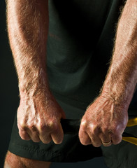 man's arms holding tennis racket