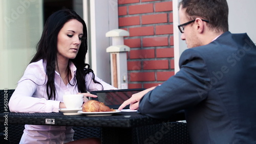 Businesswoman showing something on tablet to businessman