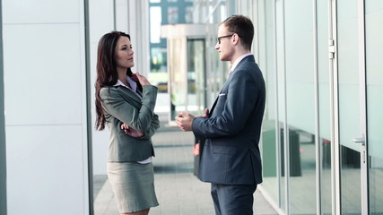 Businesswoman and businessman talking by the office building