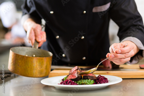 Chef in hotel or restaurant kitchen cooking - 56353263