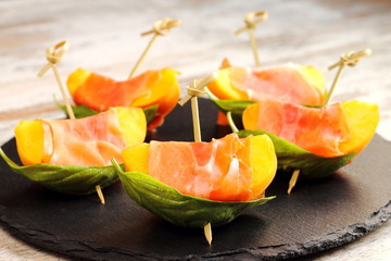 Brochettes of peaches, prosciutto and basil. Spanish tapas