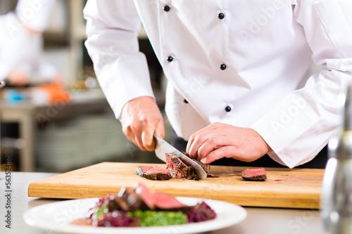 Chef in restaurant kitchen preparing food - 56353402