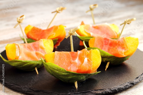 Brochettes of peaches, prosciutto and basil. Spanish tapas © mariontxa