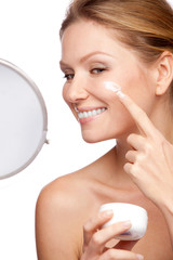 Woman applying cosmetic  cream on a clean fresh face