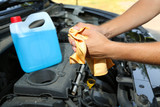 Motor mechanic cleaning his greasy hands after servicing car