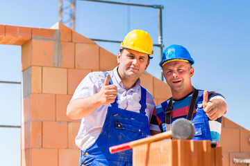 Construction site workers building walls on house