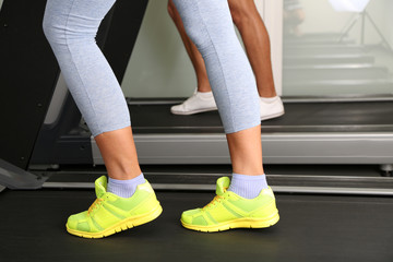 Women and men feet on treadmill close-up