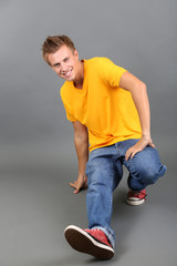 Handsome young man dancing on grey background