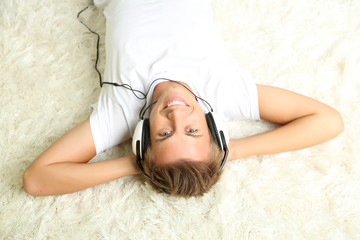 Young man relaxing on carpet and listening to music