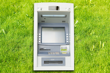 Cash dispenser on green grass