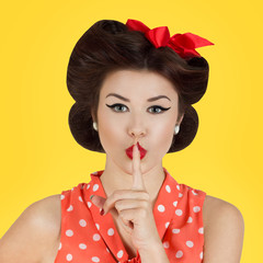 Pin-up style girl with finger on lips