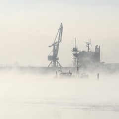 Cargo ship and cranes silhouettes in fog