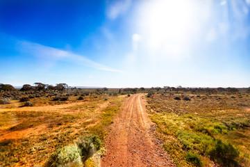 Gravel road in Australian outback in bright sunshine