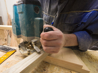 Man using router on plank of wood