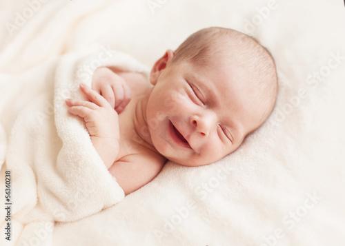 Leinwanddruck Bild Newborn baby girl asleep on a blanket.