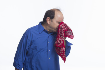 Man sneezing into handkerchief, horizontal