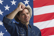 Man tilting his hat in front of American flag, horizontal
