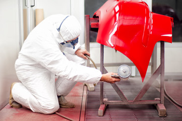 Auto mechanic painting with spray gun a car in paint booth