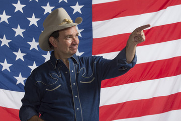 Cowboy pointing in front of American flag, horizontal