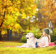 Female lying on a green grass with her dog in a park