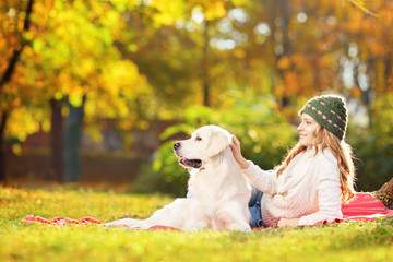 Female lying on a grass with her dog in a park