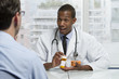 Doctor consulting patient with prescription bottle, horizontal