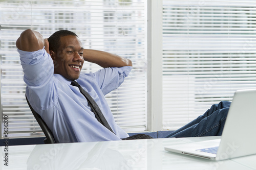 African-American business man taking a break at desk, horizontal