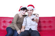 Christmas couple watching TV sitting at sofa