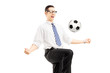 Young happy businessman playing with a soccer ball