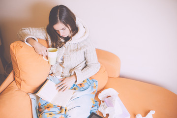 Sick young woman reading book and drinking tea on couch