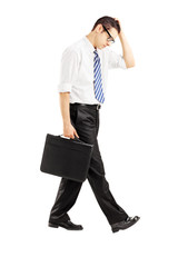 Disappointed businessman walking with briefcase