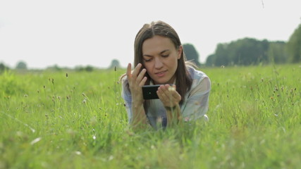 Young woman lying on the grass and texting in the park