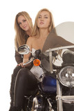 Two women on motorcycle close up serious