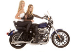 Two women sit motorcycle side