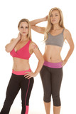 Two women sports bras fitness stand