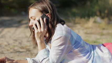Young attractive woman talking on mobile phone outdoors