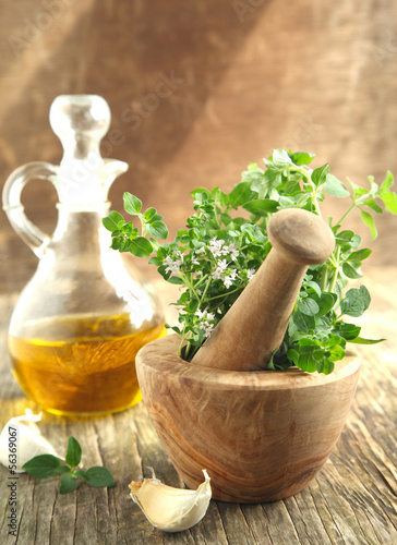 Oregano herb in wooden mortar and pestle.