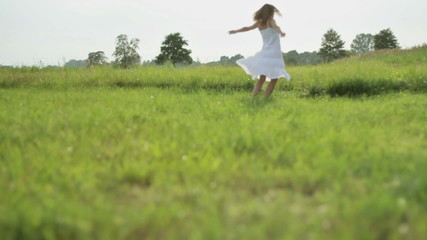 Carefree young woman on the grass, slow motion