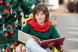 Boy With Book Sitting Against Christmas Tree