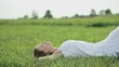 Beautiful young brunette woman lying on the meadow