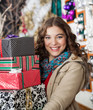 Woman Carrying Stacked Christmas Presents In Store
