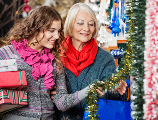 Mother And Daughter Buying Christmas Decorations