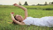 Young smiling woman relaxing on a green meadow, slow motion